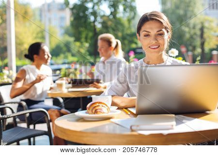 Favorable ambience. Beautiful smiling woman sitting in a cafe and working on her project on the laptop while two colleagues watching video on tablet in the background