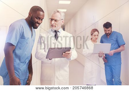 Work together. Confident professor wearing glasses and holding his gadget in both hands while looking at his intern
