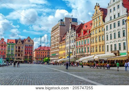 Wroclaw/Poland- August 17, 2017: cityscape of old town Market Square with colorful historical buildings, outdoors restaurants  sunshades, tourists walking and sitting on benches and blue sky