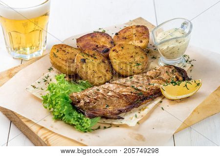 Fish fillet, fried potatoes with greens, lemon and sauce on a wooden board. A glass of light beer and a ready fish dish on a white wooden table
