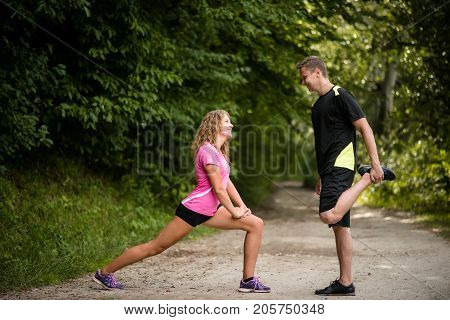 Young joggers warming up by doing leg stretching exercises