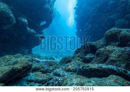 Scuba diver between rocks waiting for other divers