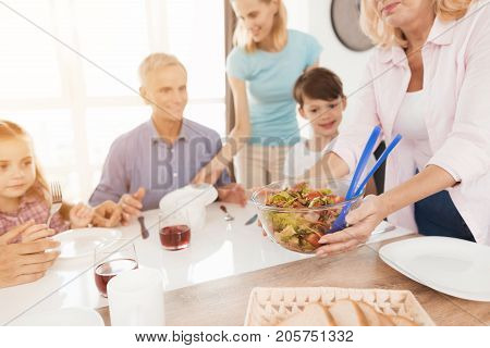 The family gathered at the dinner table for dinner. A middle-aged woman serves a salad on the table. Everyone looks at him with impatience