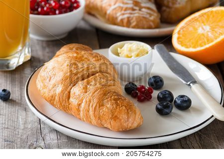 Continental breakfast fresh croissants with butter, glass of orange juice, jam and fruits on wooden table. Closeup view, horizontal