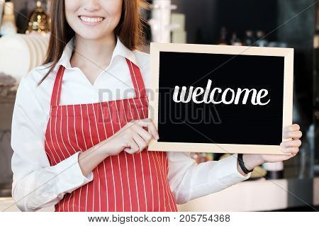 Women holding welcome sign board at cafe background small business owner food and drink industry concept
