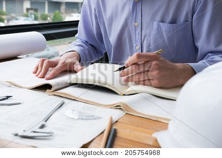 Architect Working On Construction Plan At Office. Engineer Inspect Blueprint At Workplace. Man Sketc