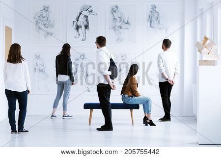 Visitors in art gallery with drawings and sculpture during cultural meeting. Art gallery concept poster