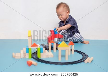 Cute Asian 20 months / 1 year old toddler baby boy child play with colorful wooden blocks. Kid playing with educational toys at home isolated with copy space
