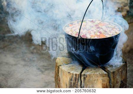 Cooking in cauldron on Finnish, Swedish log stove