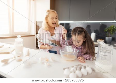 The girl whacks the dough with a whisk in a glass bowl. A woman stands next to her and holds a book with recipes in her hands.