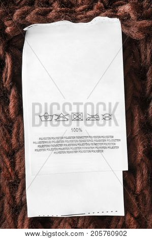 Washing instructions and fabric composition clothes label on brown knitted background