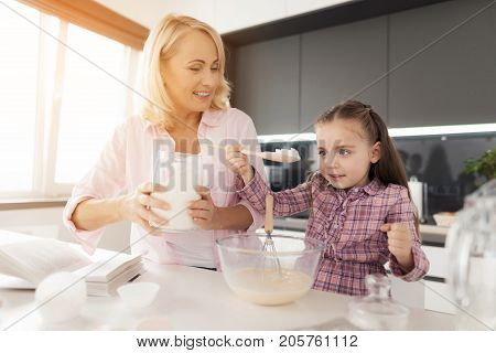 A girl with her grandmother cooks a homemade cake. Grandma is holding a jar of flour, a girl is pouring flour into the dough