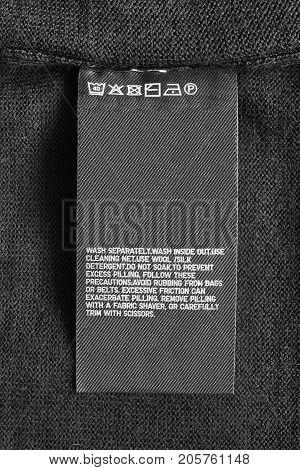 Washing instructions clothes label on black wool background