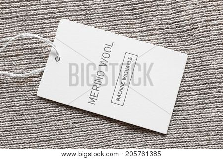 Fabric composition clothes label on beige wool background closeup
