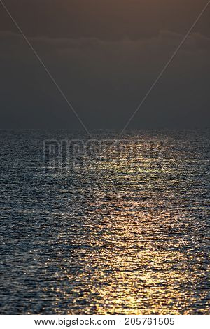Early morning orange sunlight reflecting off calm sea water. Serene peaceful background travel and tourism image with copy space. Calm before the storm.