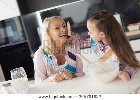The girl and her grandmother fool around making home-made pie. The girl laughs and licks her grandmother with a test, Grandmother sits next to her and laughs. They are happy