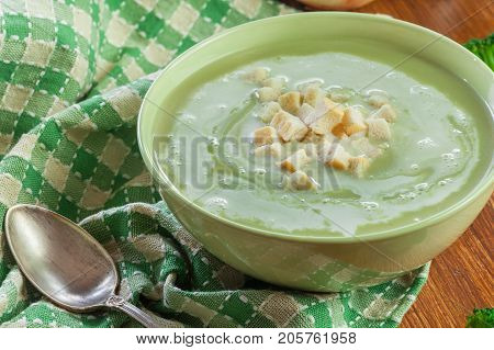 Broccoli Cream Soup In Green Bowl Served With Croutons