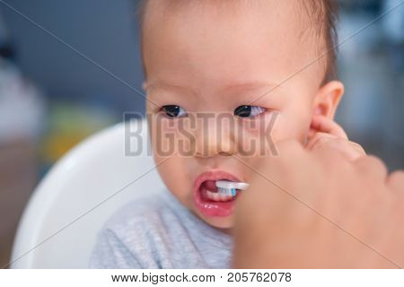 Close up portrait of Asian Father teaching kid teeth brushing Dad brushed Cute little Asian 18 months / 1 year old baby boy child's teeth in the morning at home Child development concept - Selective focus at kid's eye