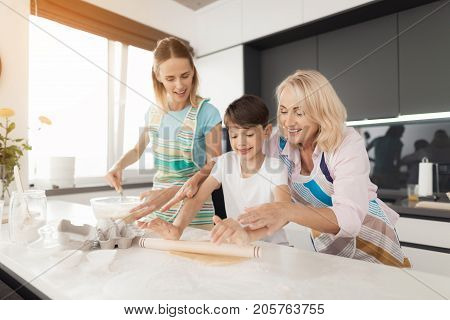 A woman is teaching her son to cook homemade cookies. Grandmother helps them. A boy with a rolling pin in his hand unrolls the dough on the table top. Grandmother helps him
