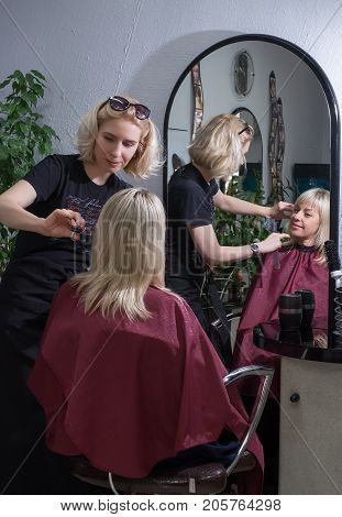 Hairdresser Rostov on Don Russia October 6 2016 A blonde woman in a hairdresser who does a haircut for a new hairdresser. Reflection in the mirror.