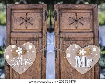 Old wooden shutter windows with hanging hearts for Mrs and Mr. Vintage decoration for weddings