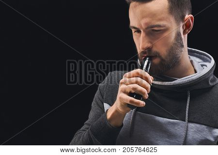 Man with vape at black studio background closeup. Young guy smoking e-cigarette to quit tobacco. Nicotine free smoking and vapor concept, copy space