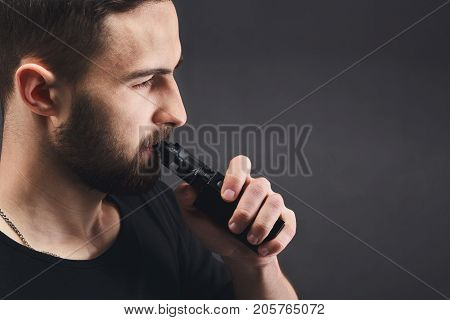 Man with vape at black studio background closeup. Young bearded guy smoking e-cigarette to quit tobacco. Vapor and alternative nicotine free smoking concept, copy space, closeup