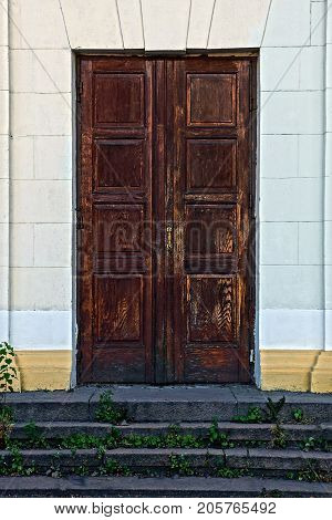 The old wooden door on the gray wall and the grass-covered threshold steps