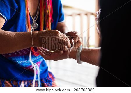 CHIANG MAI, THAILAND - SEPTEMBER 14: Unidentified elder man from Karen ethnic hill tribe minority tie guest's wrist for blessing in tying ceremony in Chiang Mai Thailand on September 14 2017.