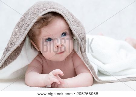 Cute baby after bath, parental care concept. Happy baby having fun. Three-months old baby looking up.