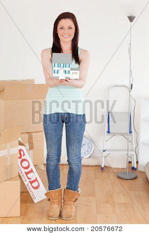 Attraktive Rothaarige Frau hält ein Miniatur-Haus auf dem Boden stehend