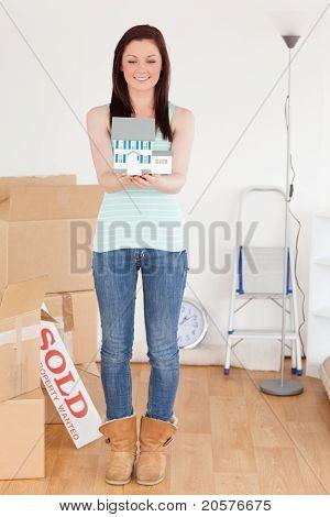 Schöne Rothaarige Frau hält ein Miniatur-Haus auf dem Boden stehend