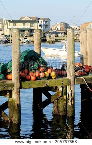 Large pile of fish nets with orange and yellow floats attached sitting on a wooden dock.