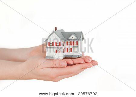 Hände halten ein Miniatur-Haus auf einem weißen Hintergrund