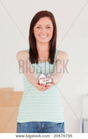 Wunderschöne Rothaarige Frau gedrückt halten ein Miniatur-Haus und auf dem Boden stehend
