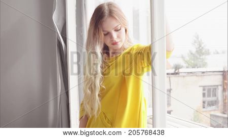 A beautiful blonde in a yellow dress with long hair stands by the window and holds her hand over the window frame