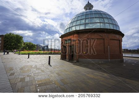 Wide angle shot from the Greenwich Foot Tunnel South entrance with a cloudy sky and buildings and a garden in the background in a cloudy day.