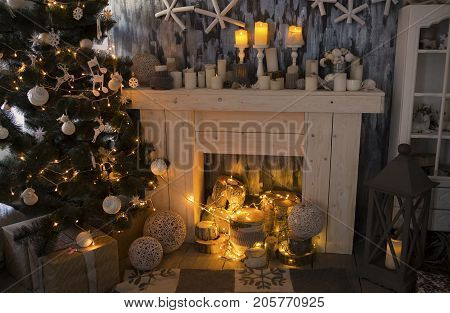 Christmas room with fireplace presents under decorated fir tree and toys in it. Fireplace Christmas decorations. Fireplace room with nobody.