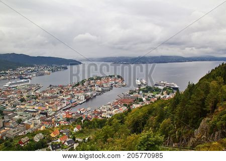 View on Bergen and harbor from the mount Floyen Norway. Cityspace. Panoramic view from hill of whole Bergen and fjord landscape. The tops of houses green trees and cloudy sky.