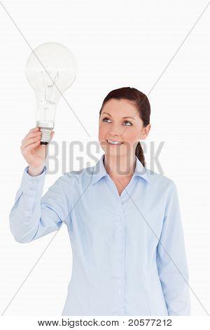 Hübsche rothaarige Frau hält eine Glühbirne stehen