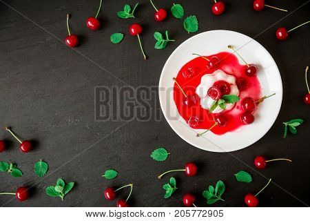 Panna cotta with cherry syrup and berries in plate on a dark background, traditional italian dessert. Flat lay. Top view