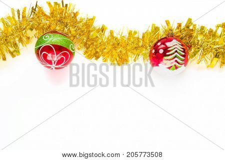 Christmas decorative red balls painted with white snow green pine tree white curved circle lines and green big line on white background together with golden yellow shiny decorations for xmas tree