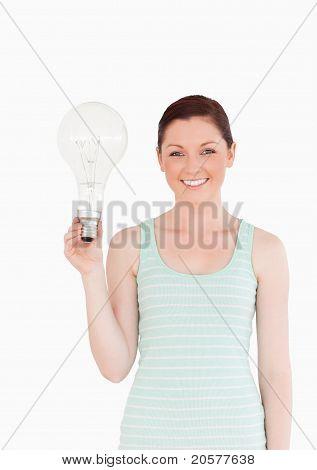 Wunderschöne Rothaarige Frau hält eine Lampe stehen