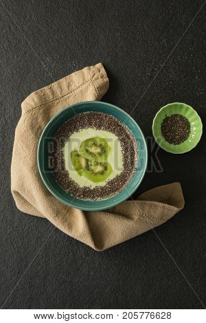 Sliced kiwifruit with milk in a bowl on concrete backgrouind