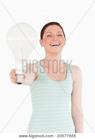 Schöne Rothaarige weibliche halten eine Lampe stehen