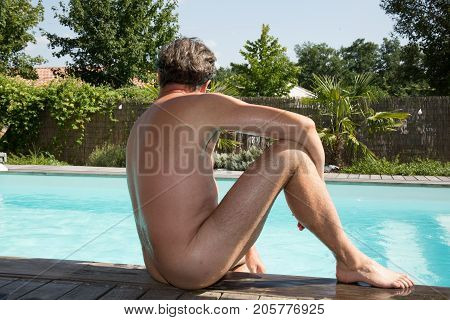 Attractive Nude Or Naked Man Resting On Edge Of Swimming Pool