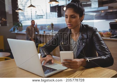 Young woman with phone using laptop at table in cafe