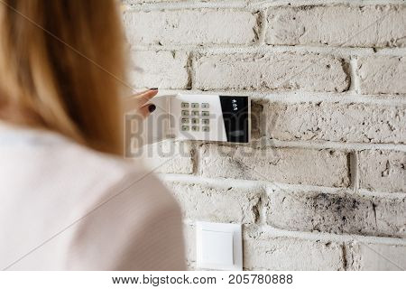 Woman Entering Password On Home Alarm Keypad.