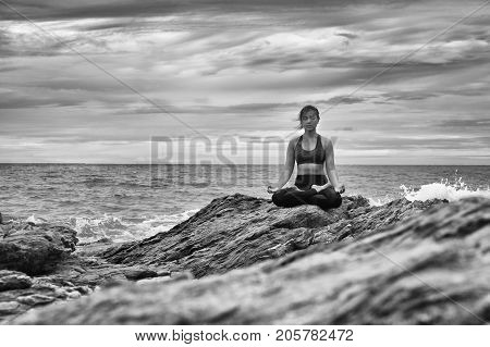 Black and white yoga on the rock at the sunset with the murmur of waves.