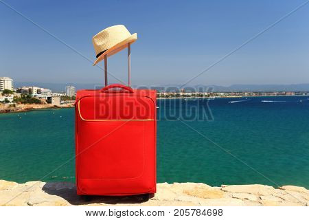 Resort and travel concept. Vacation background. Red suitcase and summer hat on sea background. Sunny summer day in salou spain resort.